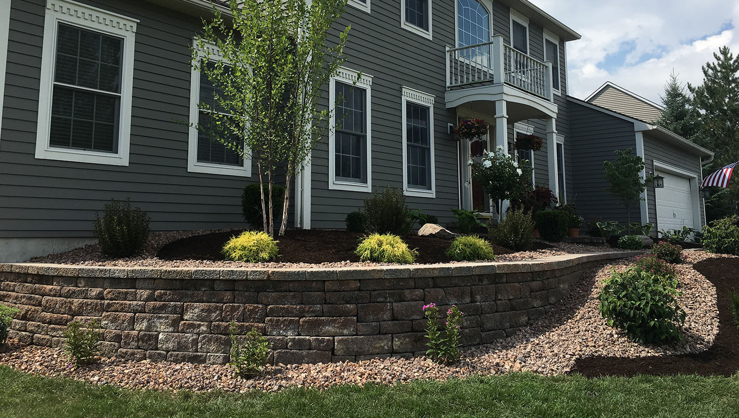 A rounded stone retaining wall at a Central New York home – sturdy enough to keep out invaders